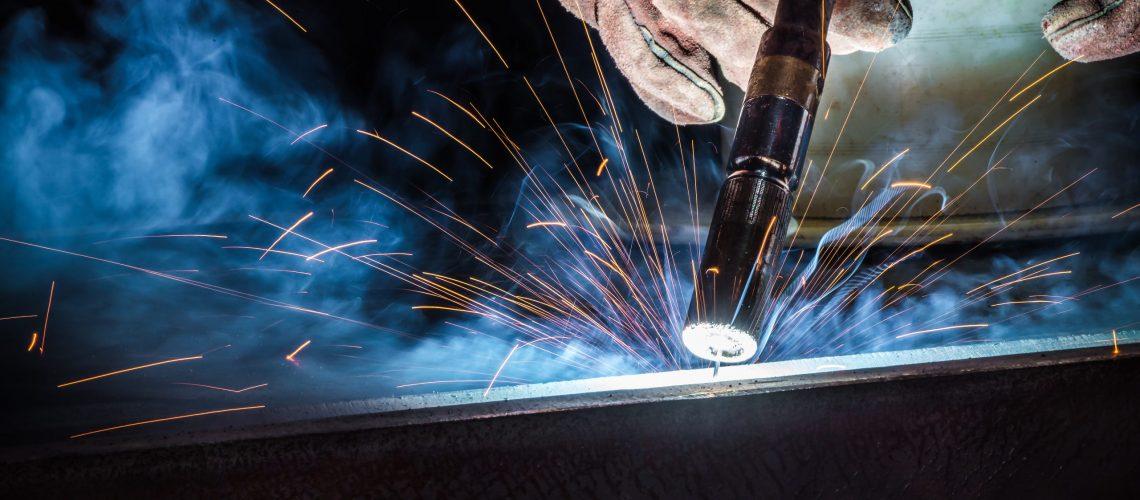 Industrial welder welding fabricated construction in factory, Welding process by Flux Core Welding, FCAW